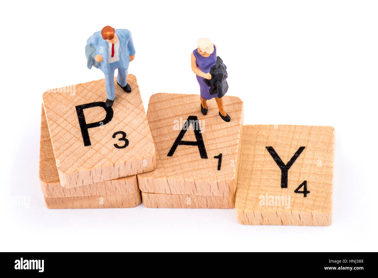 Scrabble letters make up the word PAY. A woman stands on the letter A and a  man stands above her on the letter - Stock Image