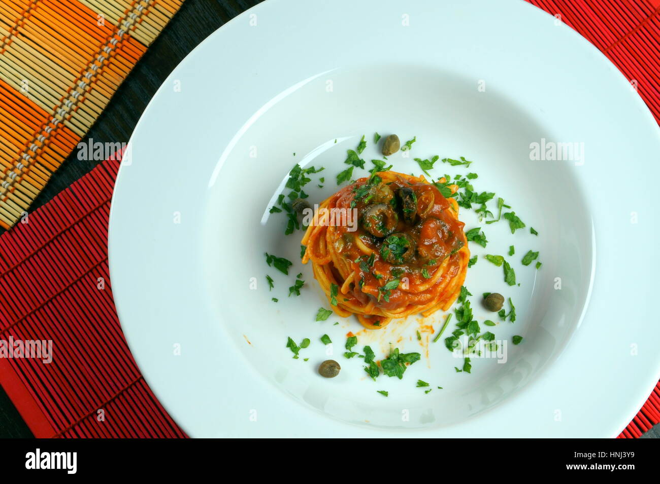 Spaghetti puttanesca on colorful placemats lying on wooden table - Italian recipe with garlic, olive oil, anchovies, Stock Photo