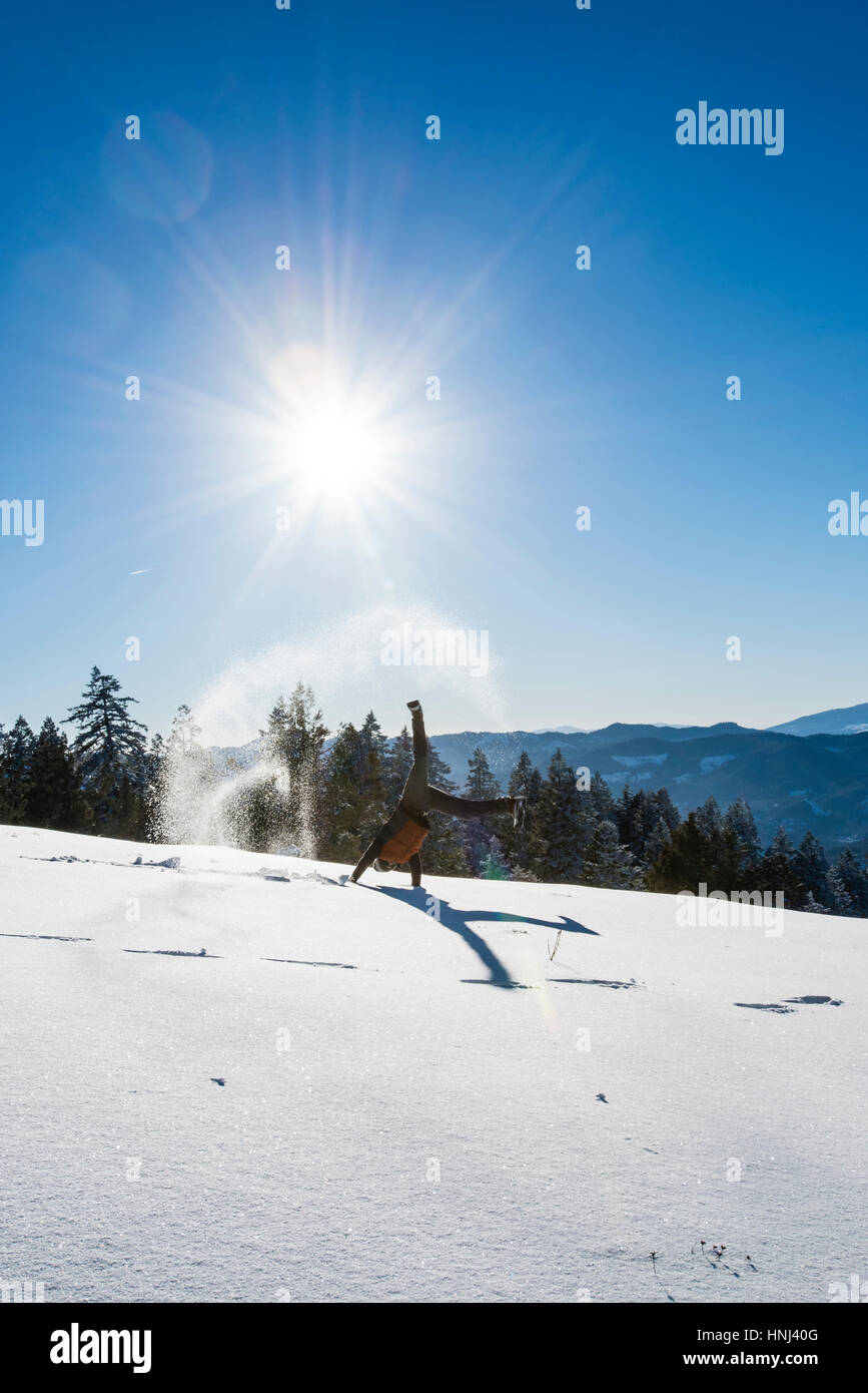 Man doing cartwheel on snowy field against sky during sunny day - Stock Image