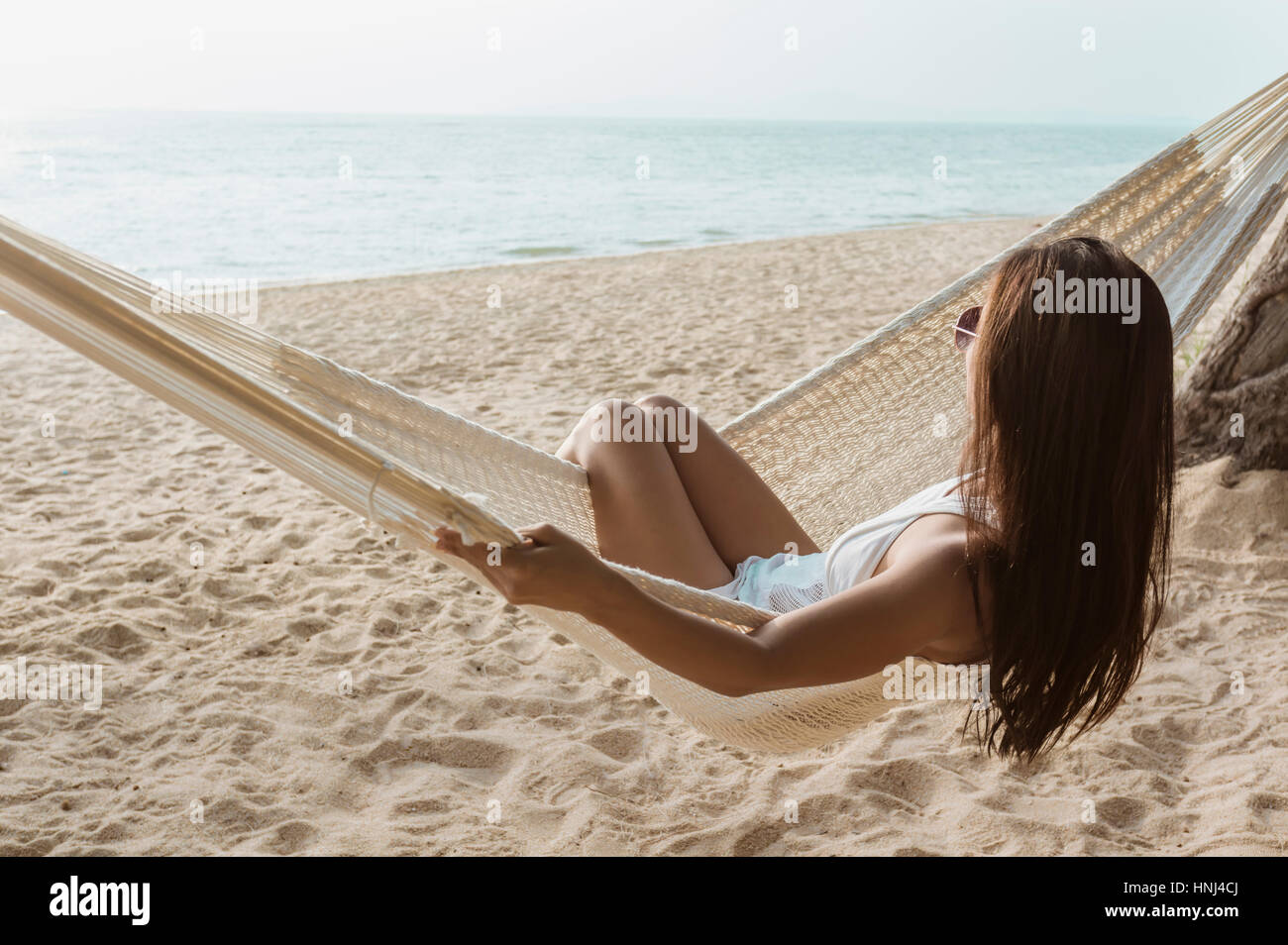 Woman relaxing on hammock at beach - Stock Image
