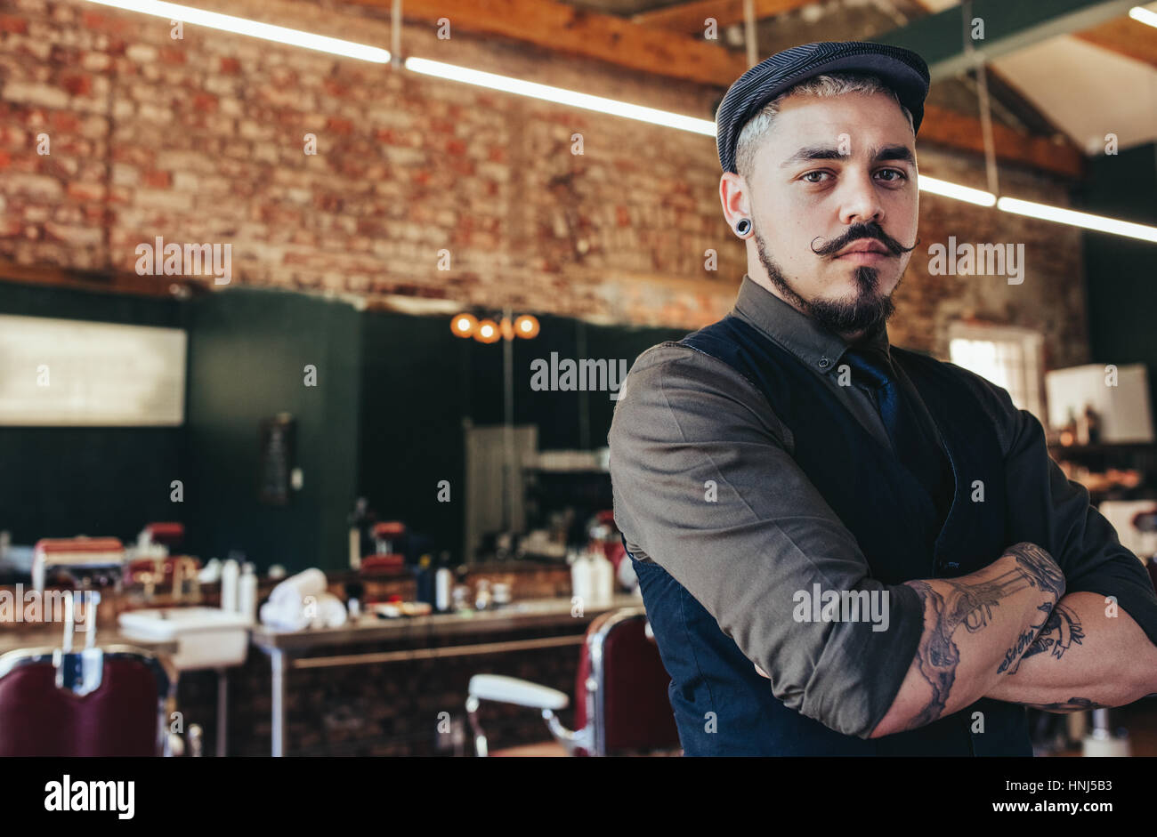 Portrait of serious looking young man standing with his arms crossed at barber shop. Male hairdresser standing in Stock Photo
