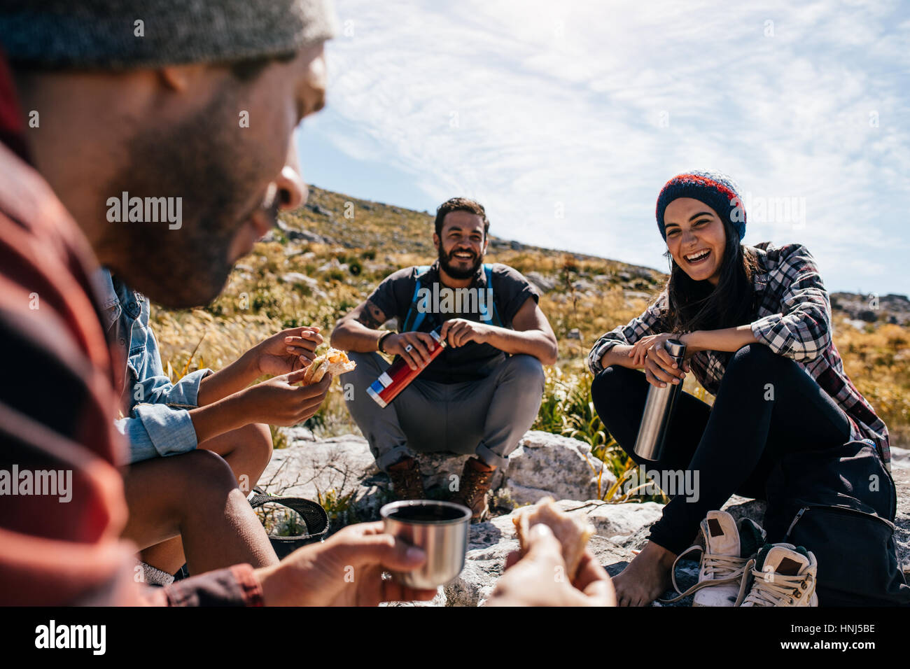 Group of people relaxing and eating during hike. Young woman with friends taking a break during a hike in countryside. - Stock Image