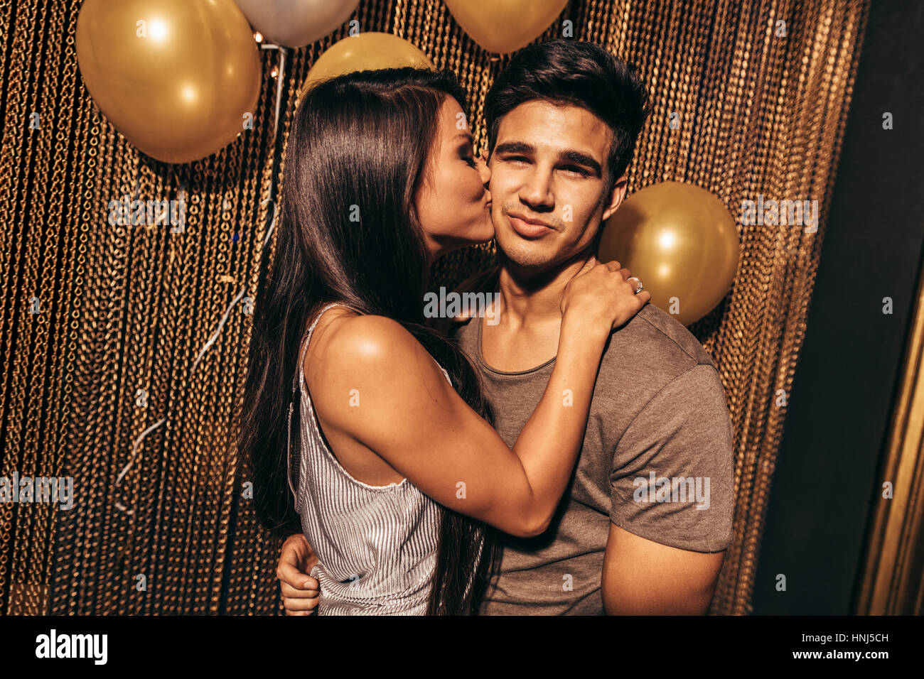Shot of loving young couple in the night club. Young woman kissing her boyfriends in the party at pub. - Stock Image
