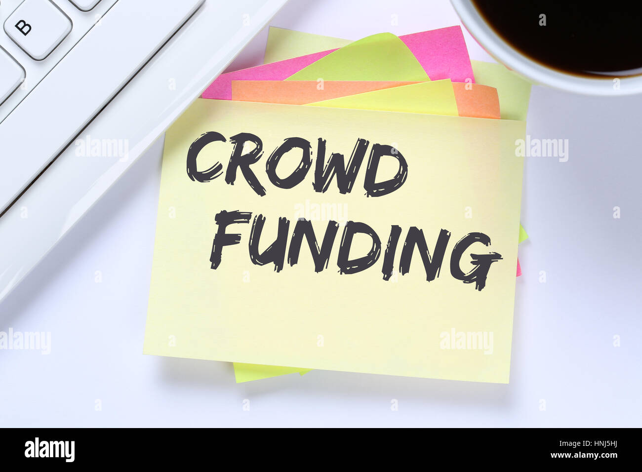 Crowd funding crowdfunding collecting money online investment internet business desk computer keyboard - Stock Image