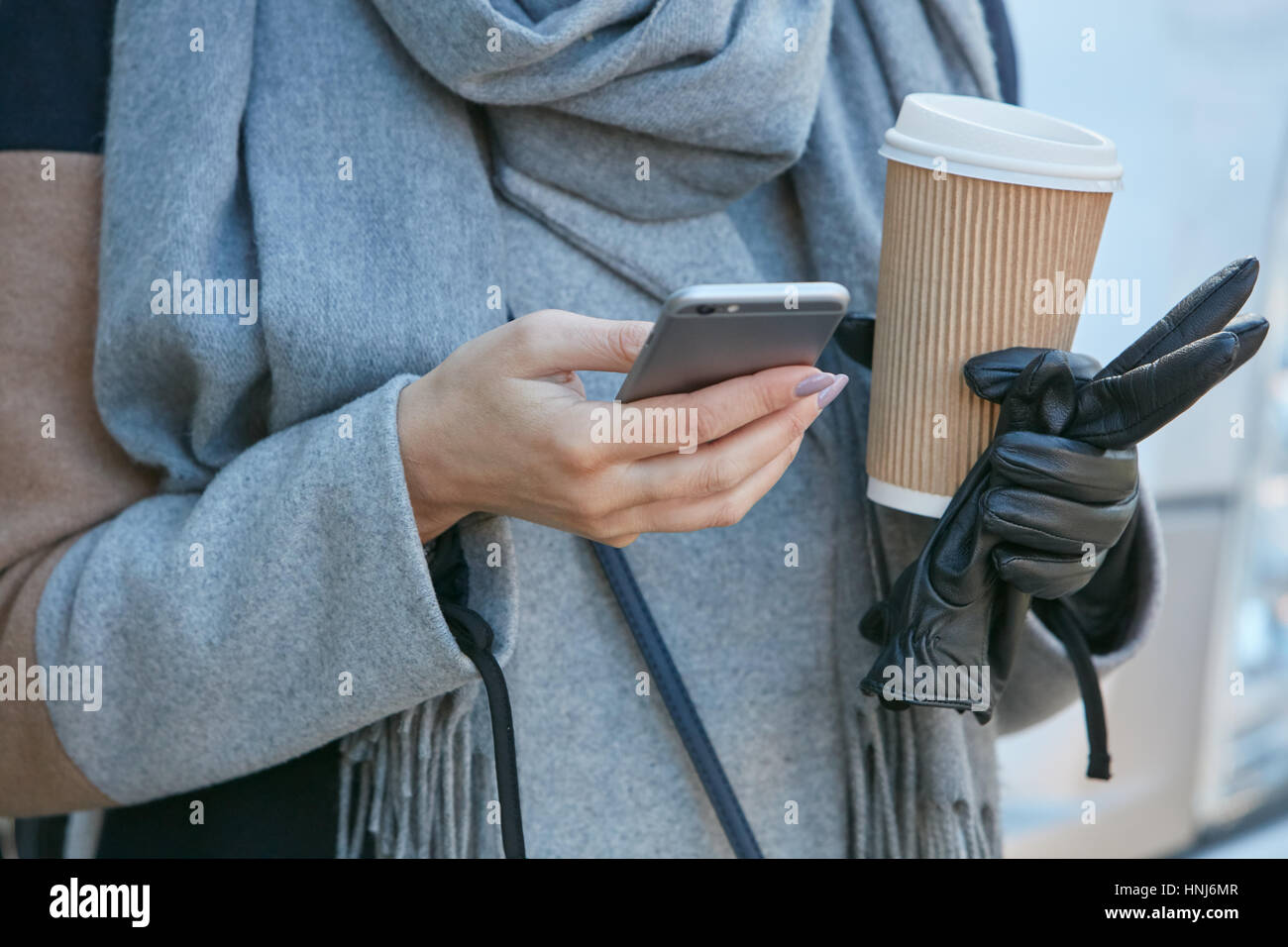 Woman looking at smartphone with coffee in hand before Emporio Armani fashion show, Milan Fashion Week street style - Stock Image