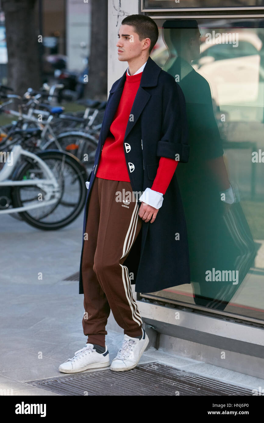 Man with brown Adidas trousers and red sweater before Emporio Armani fashion show, Milan Fashion Week street style - Stock Image