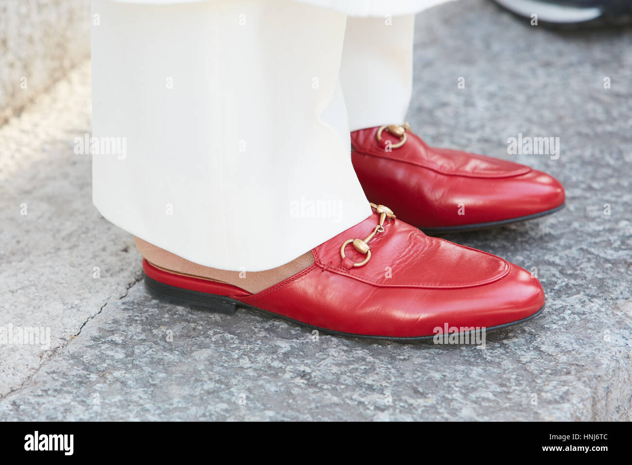 Woman with red Gucci shoes and white trousers before Emporio Armani fashion show, Milan Fashion Week street style - Stock Image