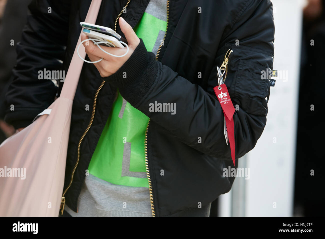 Woman with Alpha Industries black bomber jacket before Emporio Armani fashion show, Milan Fashion Week street style - Stock Image