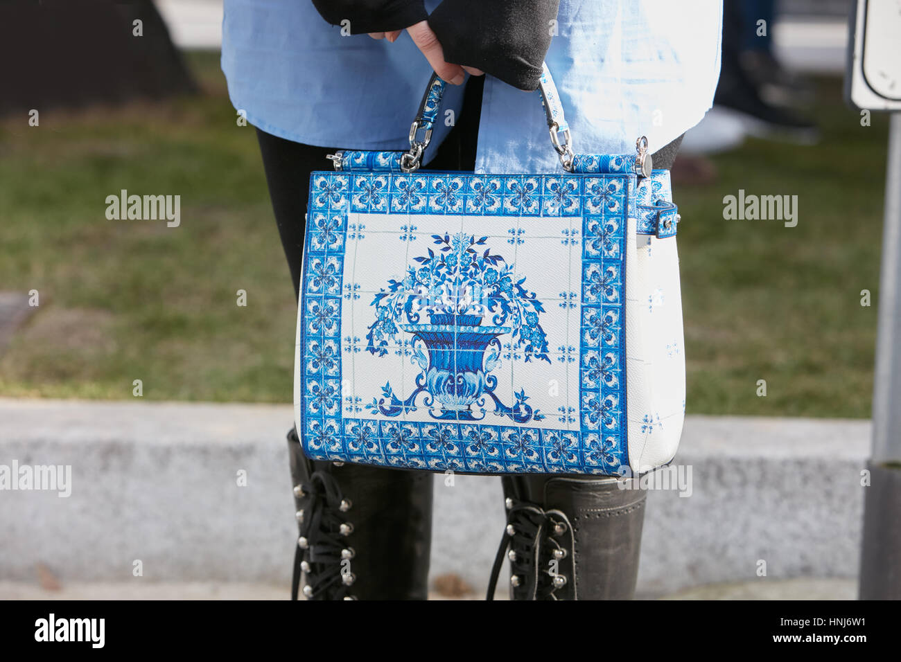 Woman with blue and white decorated bag before Emporio Armani fashion show, Milan Fashion Week street style on January - Stock Image