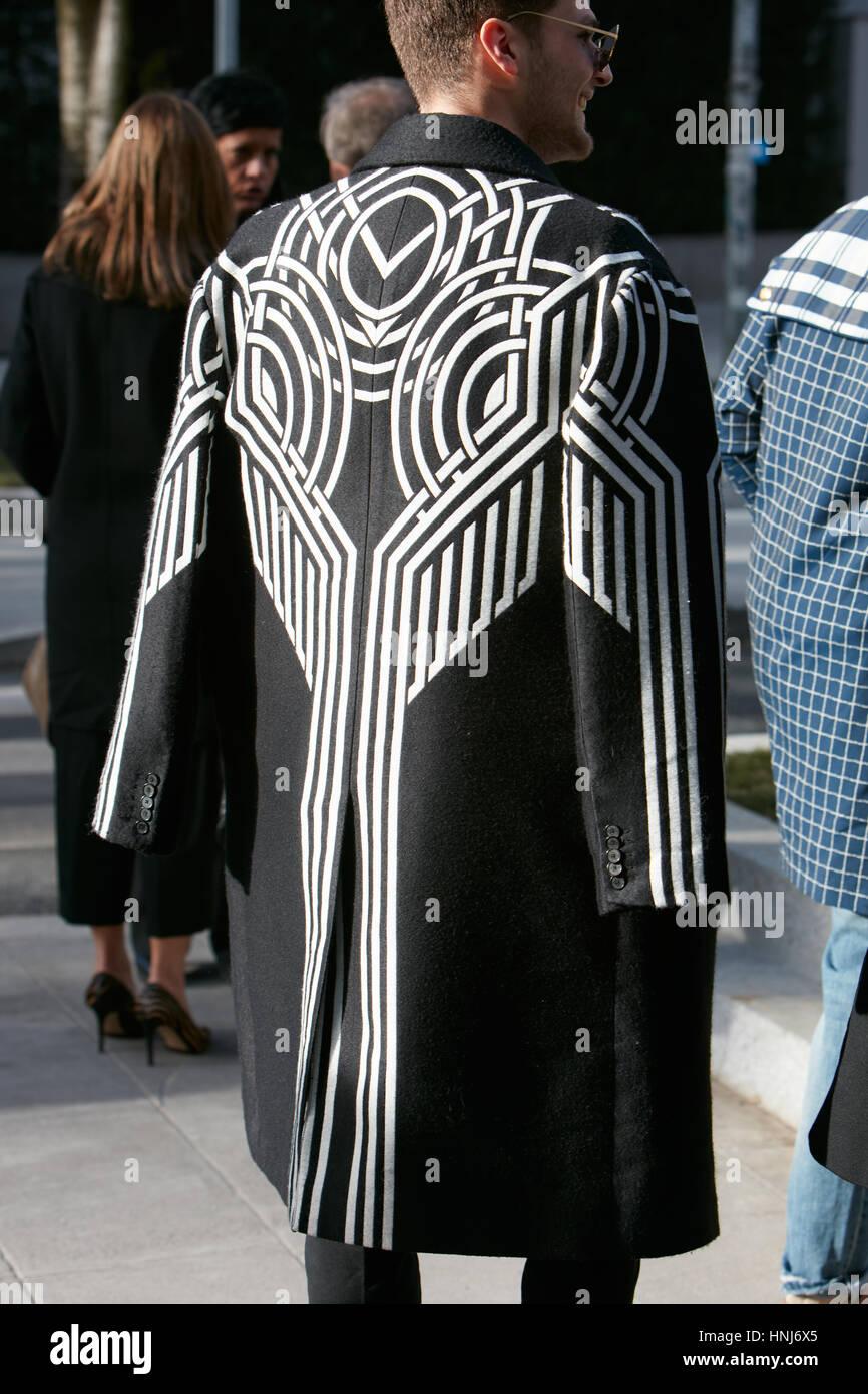 Man with black and white coat with geometric design before Emporio Armani fashion show, Milan Fashion Week street - Stock Image