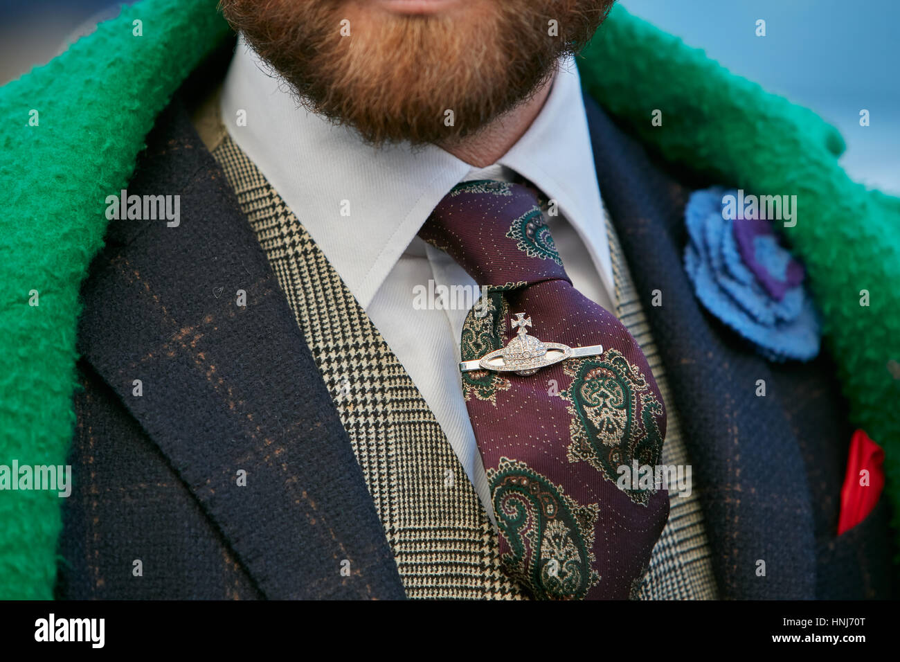 Man with green jacket and Vivienne Westwood tie clip before Salvatore Ferragamo fashion show, Milan Fashion Week - Stock Image