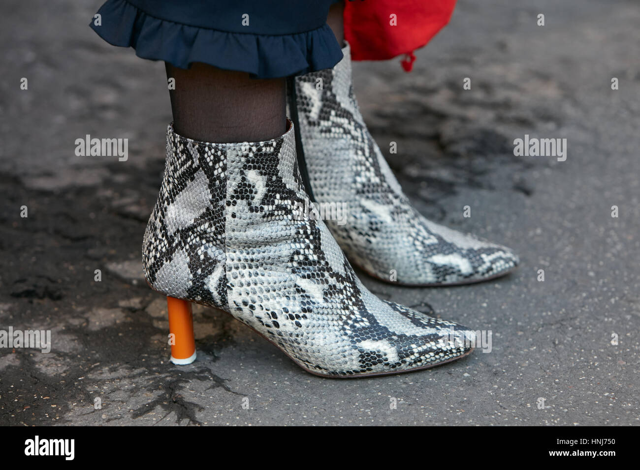 Woman with black and white snake boots with orange heel, before Salvatore Ferragamo fashion show, Milan Fashion - Stock Image