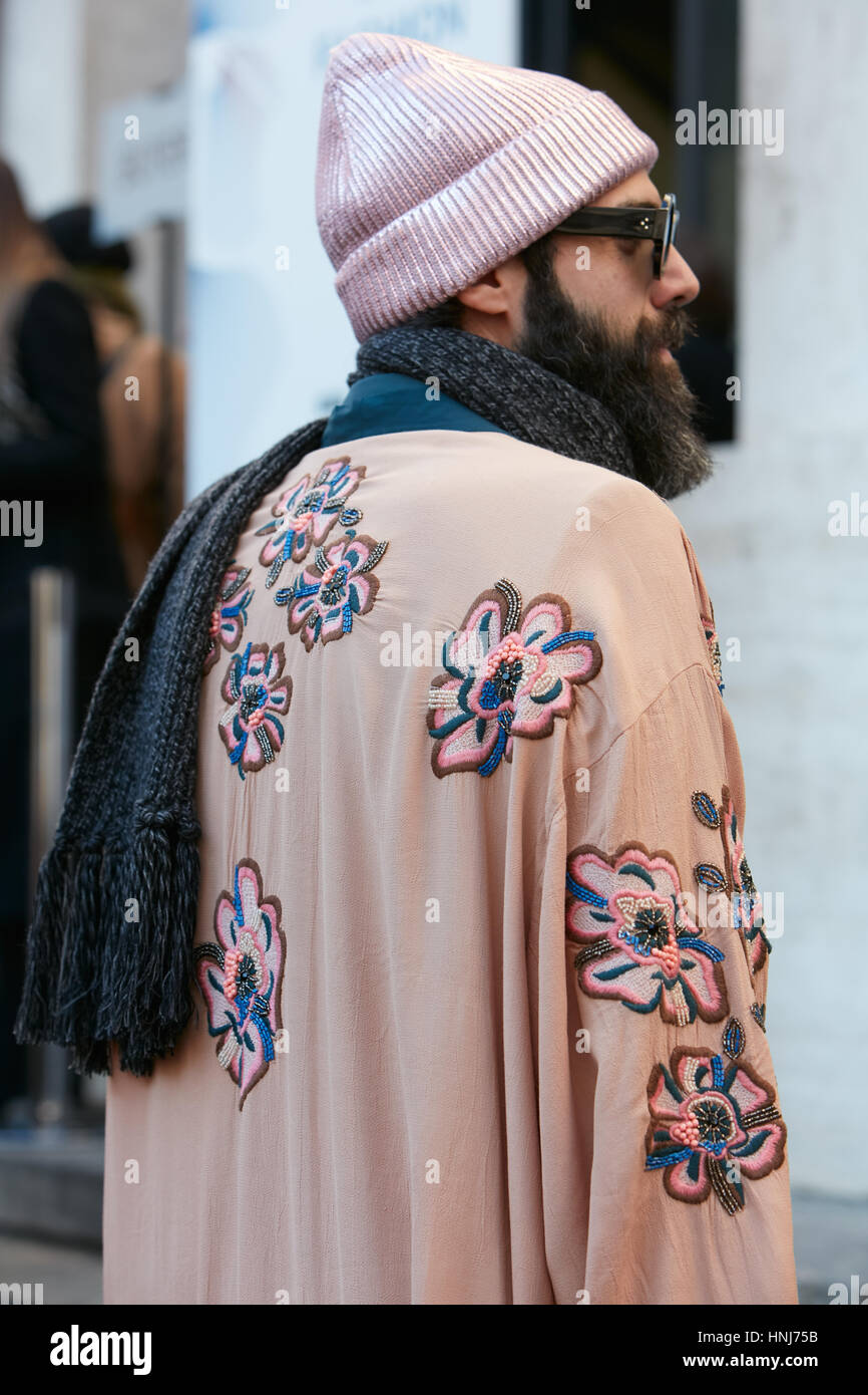 Man with pink iridescent hat and flower decorated cloak before Salvatore Ferragamo fashion show, Milan Fashion Week - Stock Image
