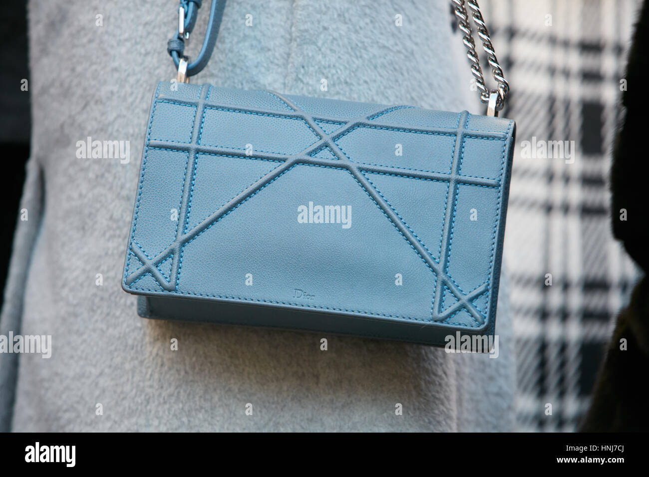 Woman with blue leather Dior bag before Salvatore Ferragamo fashion show, Milan Fashion Week street style on January - Stock Image