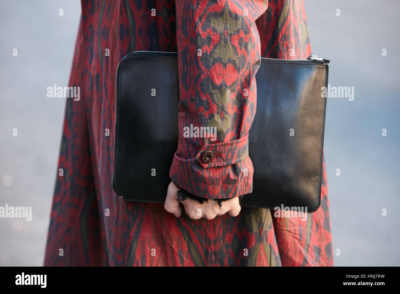 Man with red decorated trench coat and black leather bag before Etro fashion show, Milan Fashion Week street style - Stock Image