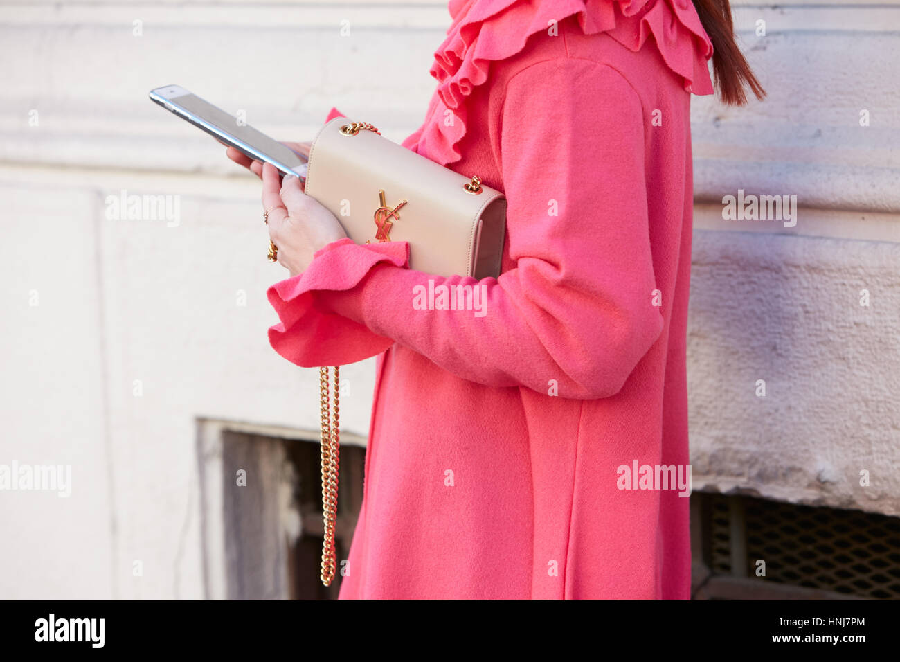 Woman with Yves Saint Laurent beige bag and pink coat before Etro fashion show, Milan Fashion Week street style - Stock Image