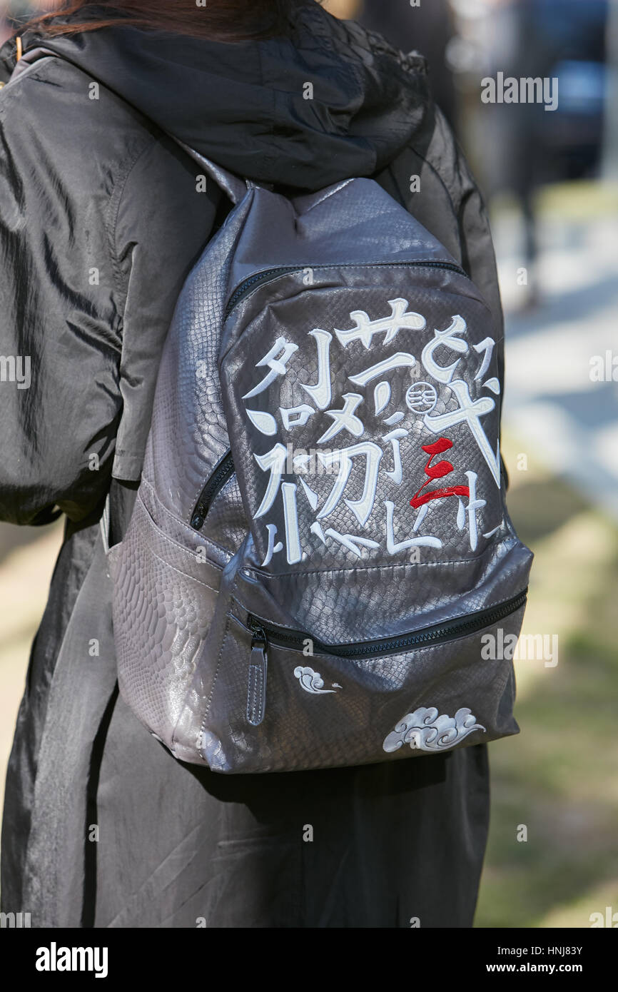 Woman with backpack with japanese writings before Giorgio Armani fashion show, Milan Fashion Week street style on - Stock Image
