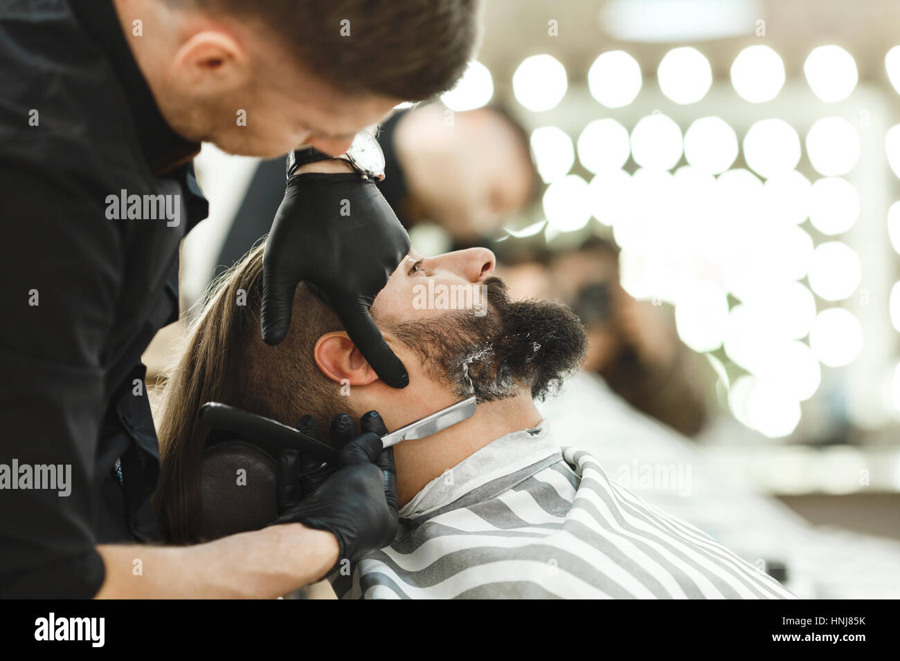 Barber making beard form for man - Stock Image