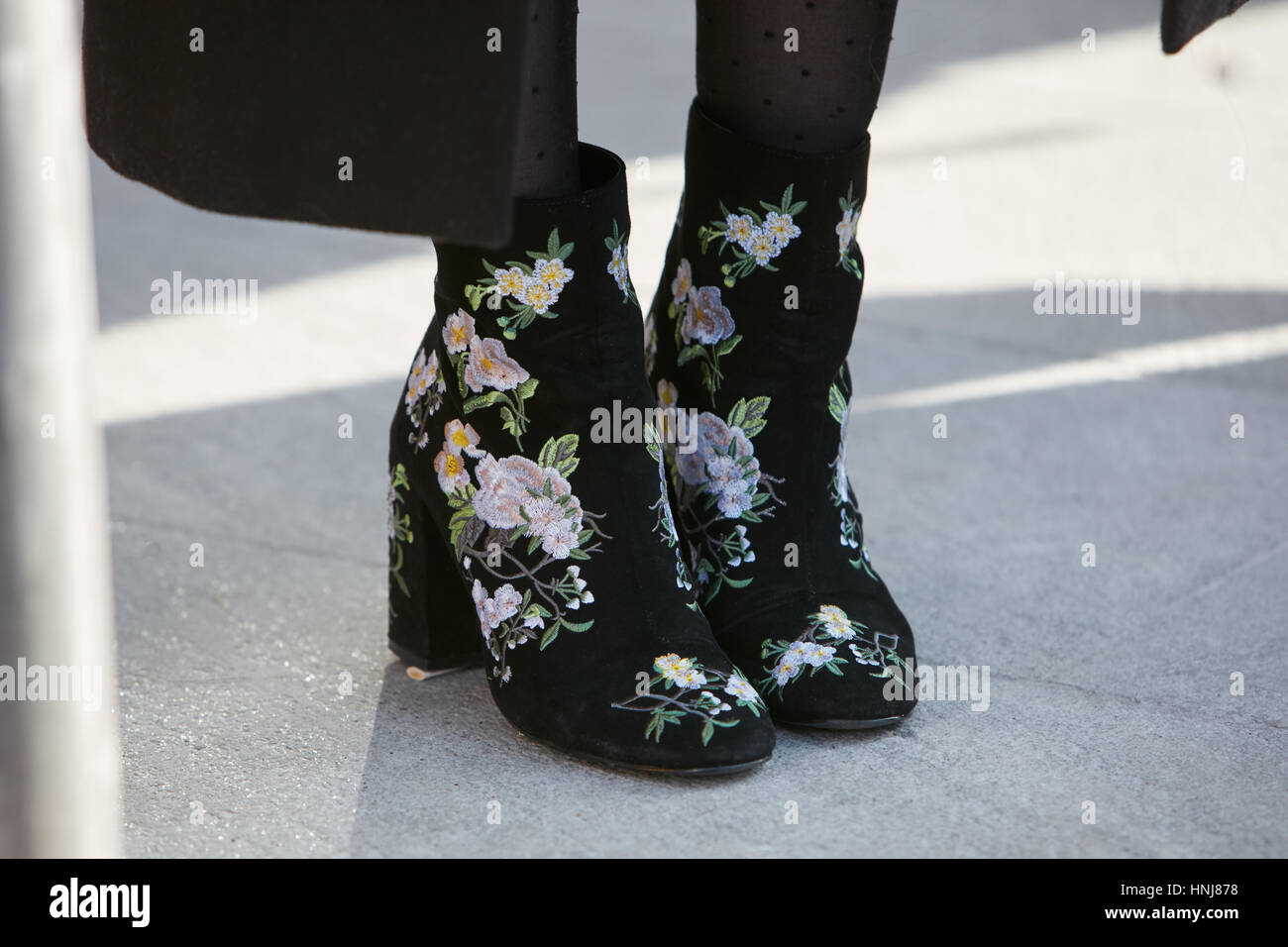 Woman with floral design shoes before Giorgio Armani fashion show, Milan Fashion Week street style on January 17, - Stock Image