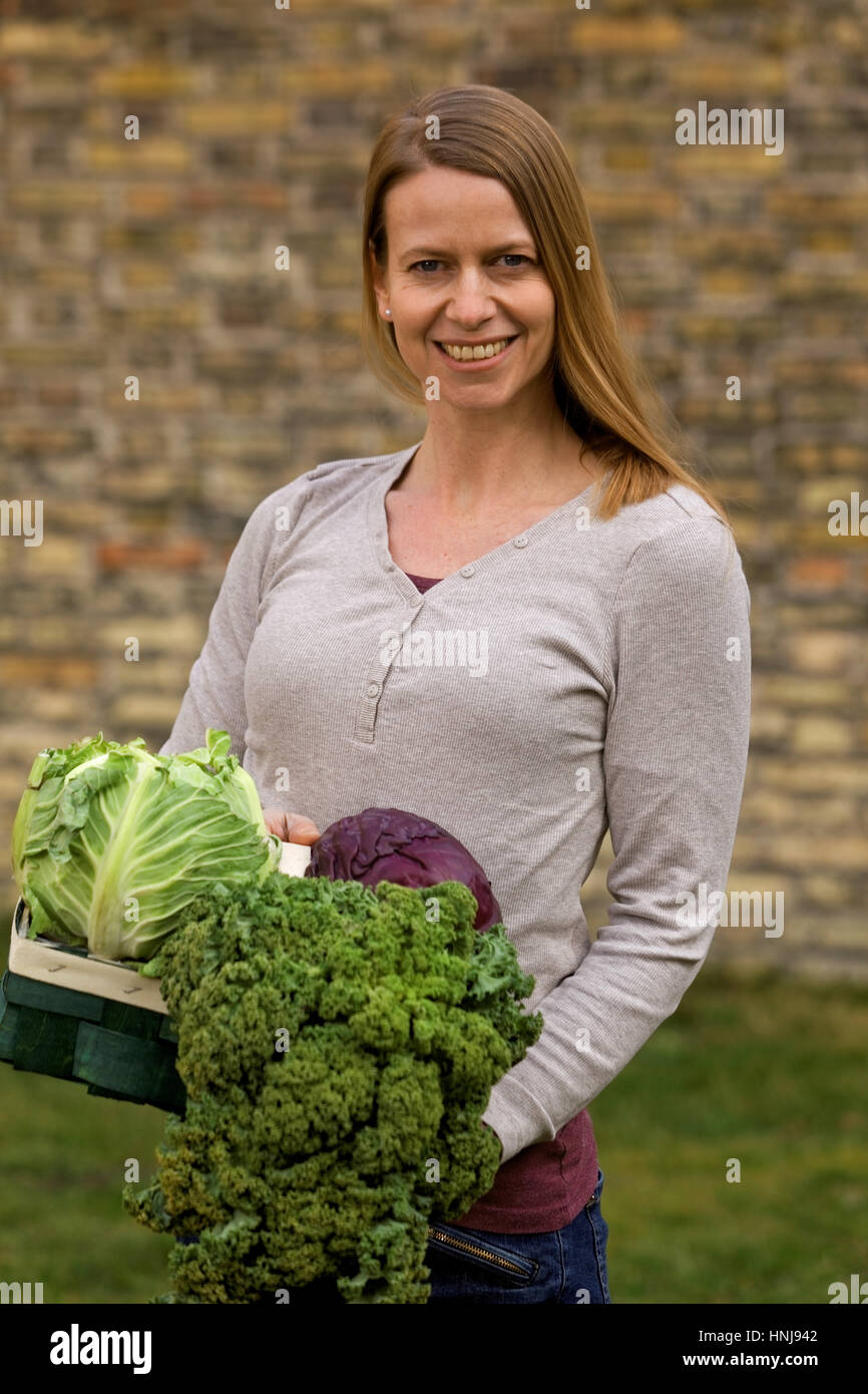 woman with winter vegetables in garden - Stock Image