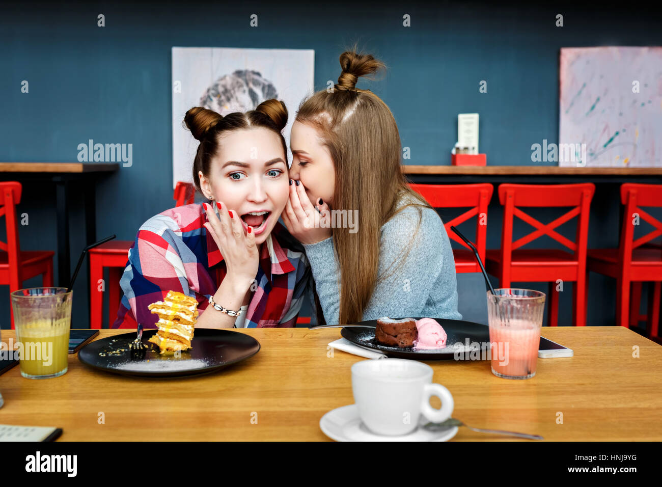 happy girl friends have cup of coffee in modern city restaurant. Stock Photo