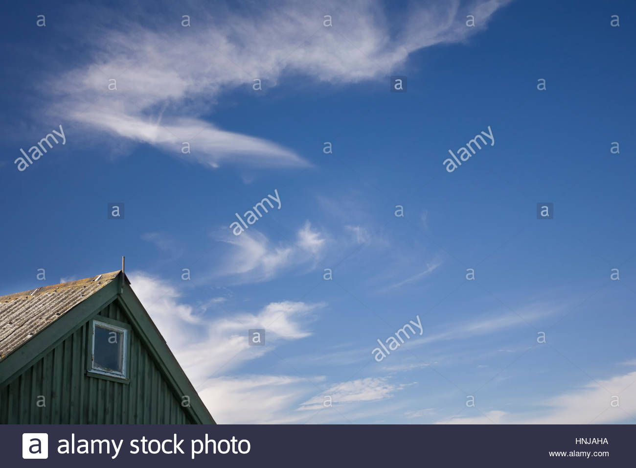 Clouds swirl above a typical swedish barn - Stock Image