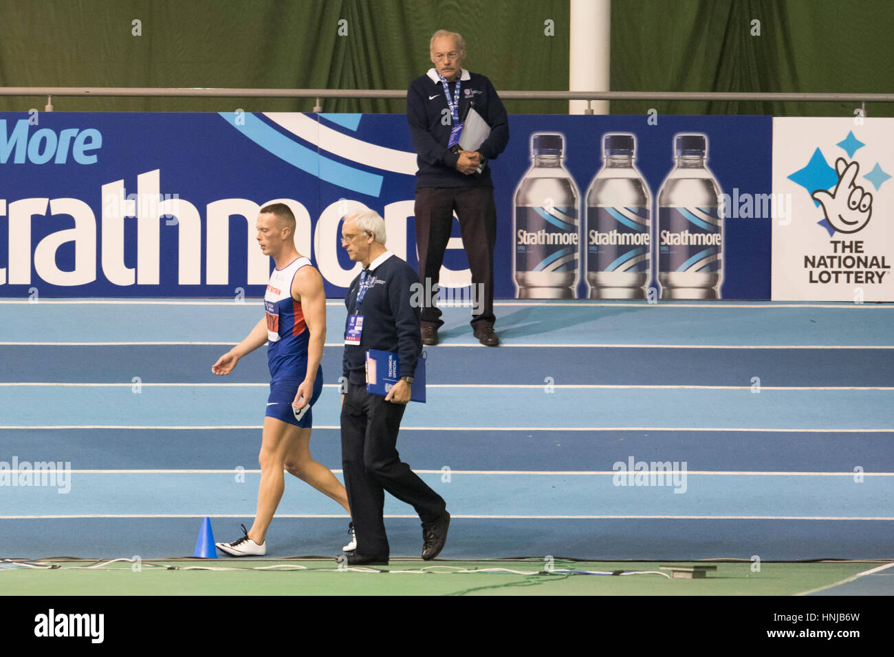 Richard Kilty is escorted off the track by an official after being disqualified for a false start in the British - Stock Image
