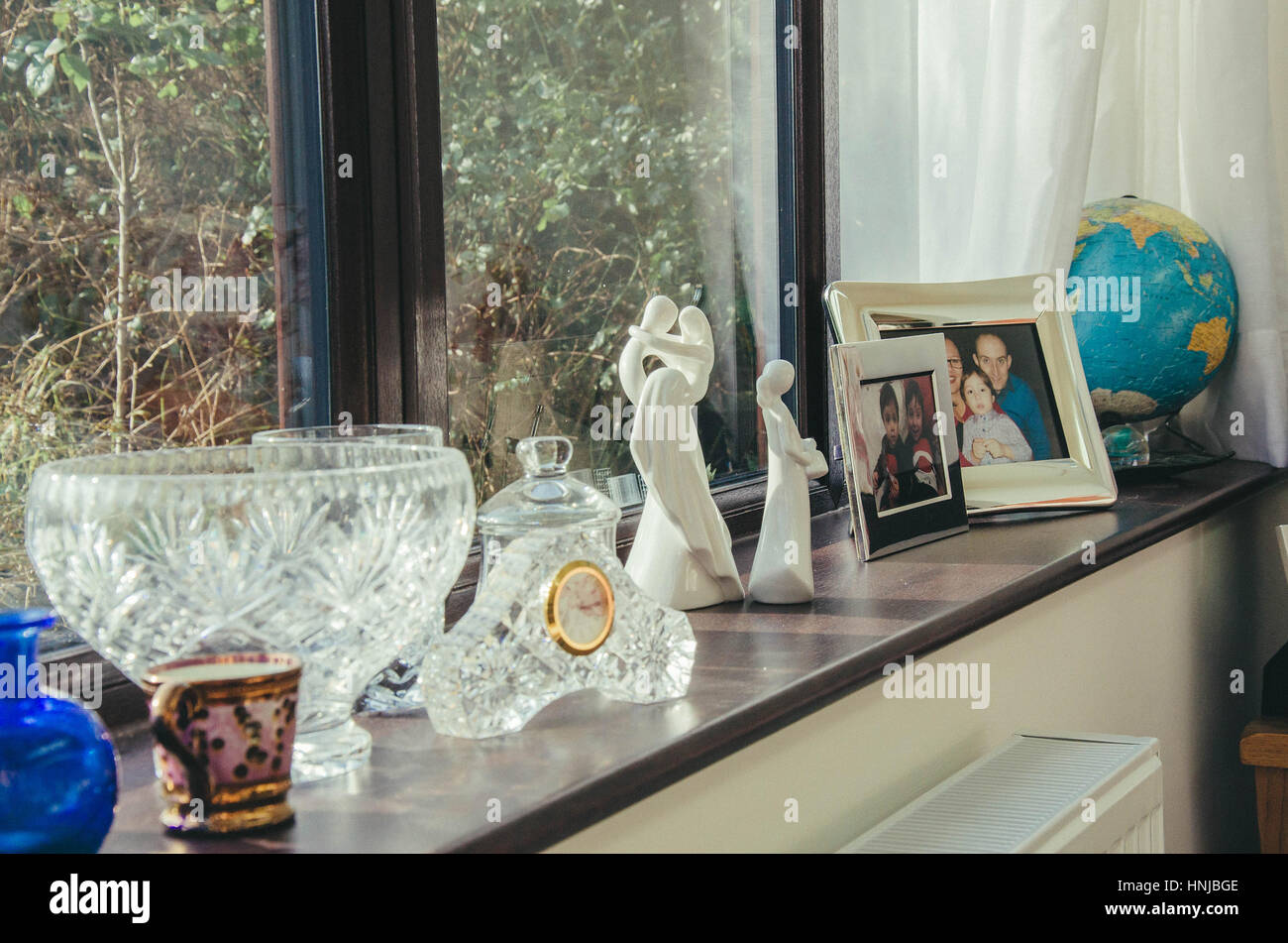 Ornaments and family photos on a window ledge. - Stock Image