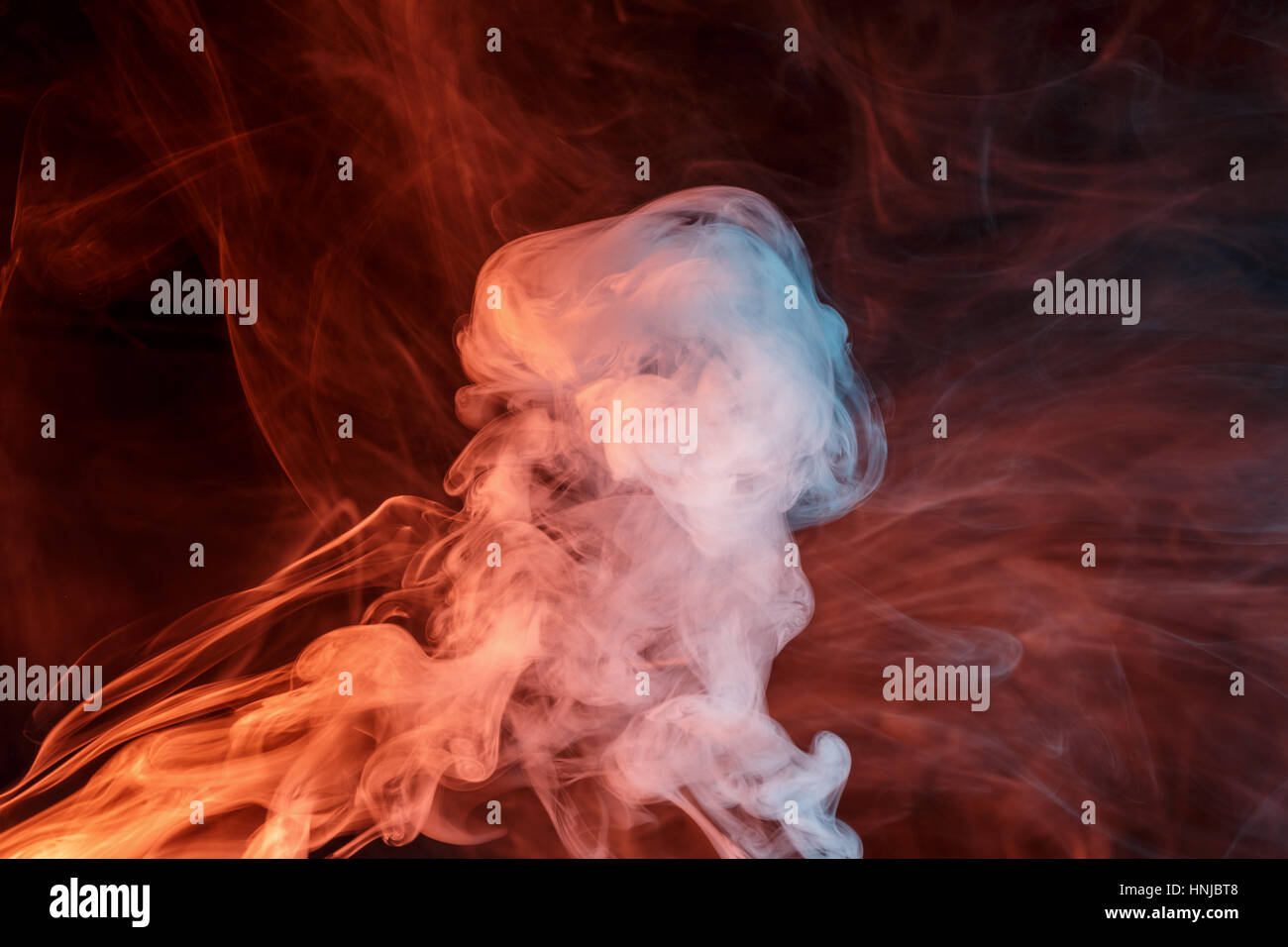 Abstract smoke Weipa. Personal vaporizers fragrant steam. The concept of alternative non-nicotine smoking. Orange - Stock Image