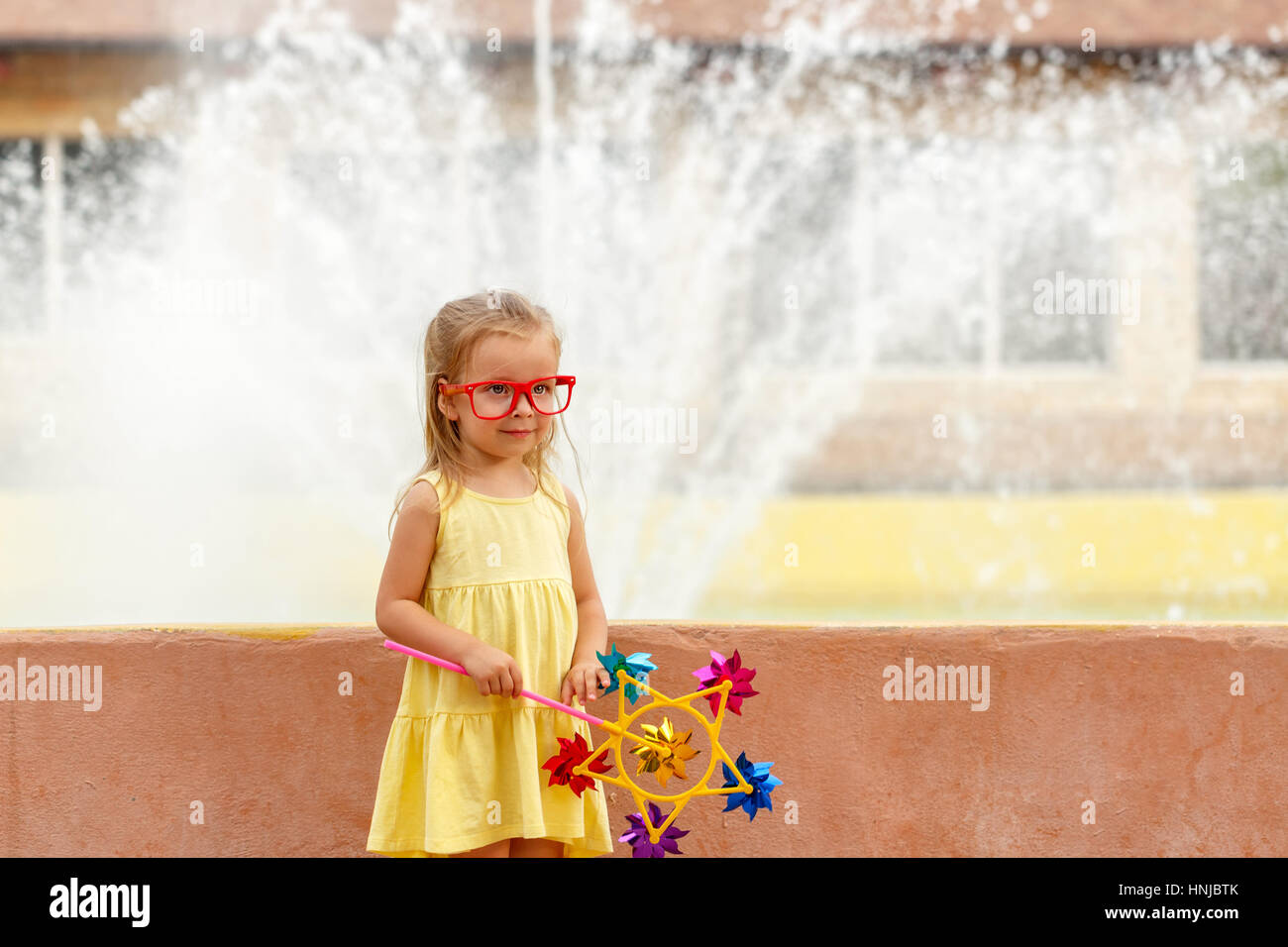 Cute little girl holding a pinwheel in hand. A walk in the summer park near the city fountain. Summer vacation. Stock Photo