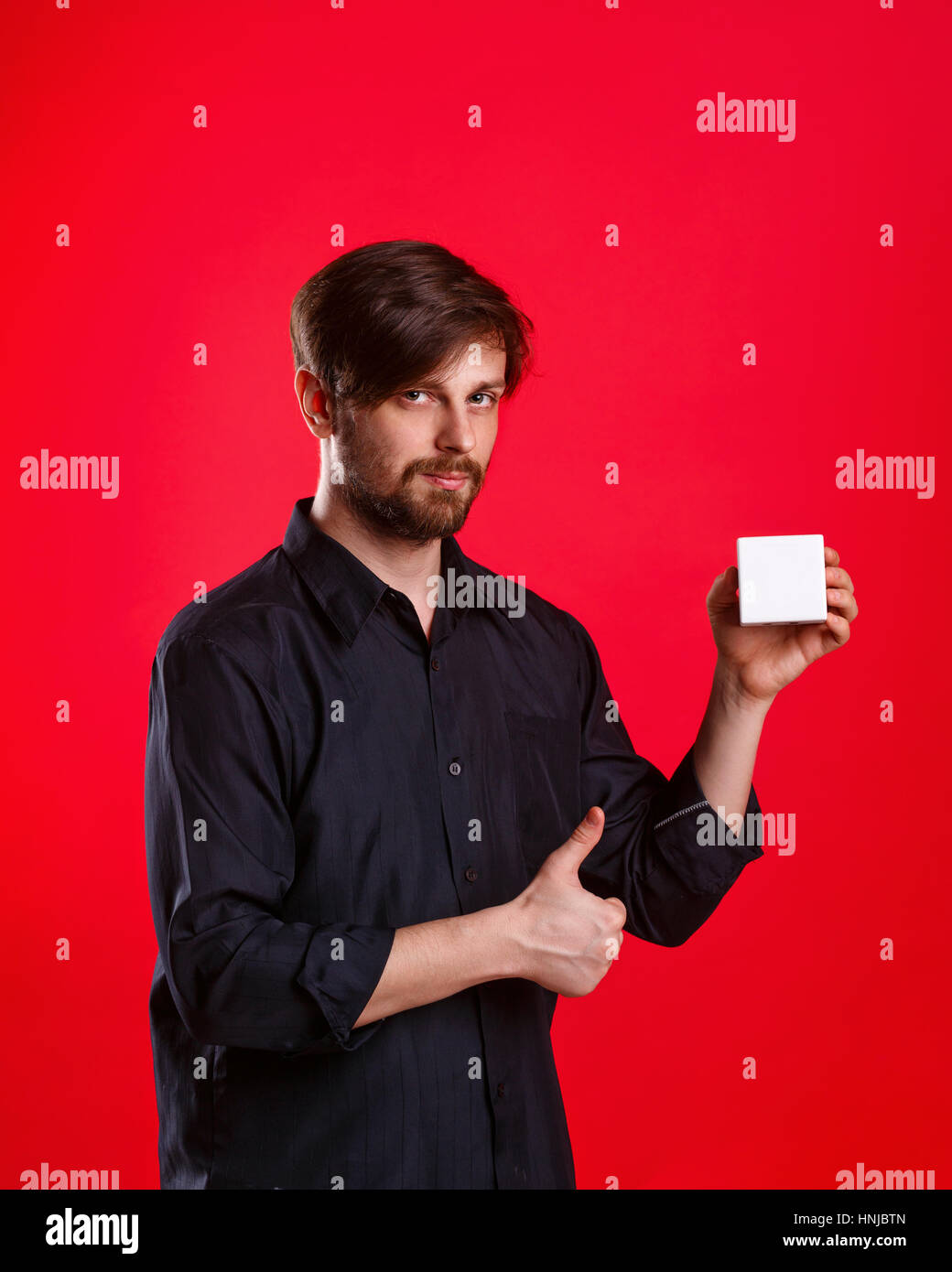 Man holding an empty cube. Advertising Space. Attractive man shows space for copy. Thumb up. Everything gonna be - Stock Image