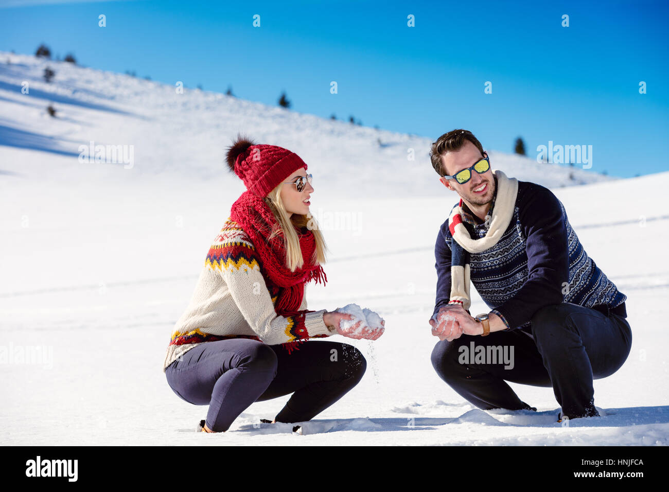 Snowball fight. Winter couple having fun playing in snow outdoors. Young joyful happy multi-racial couple. - Stock Image