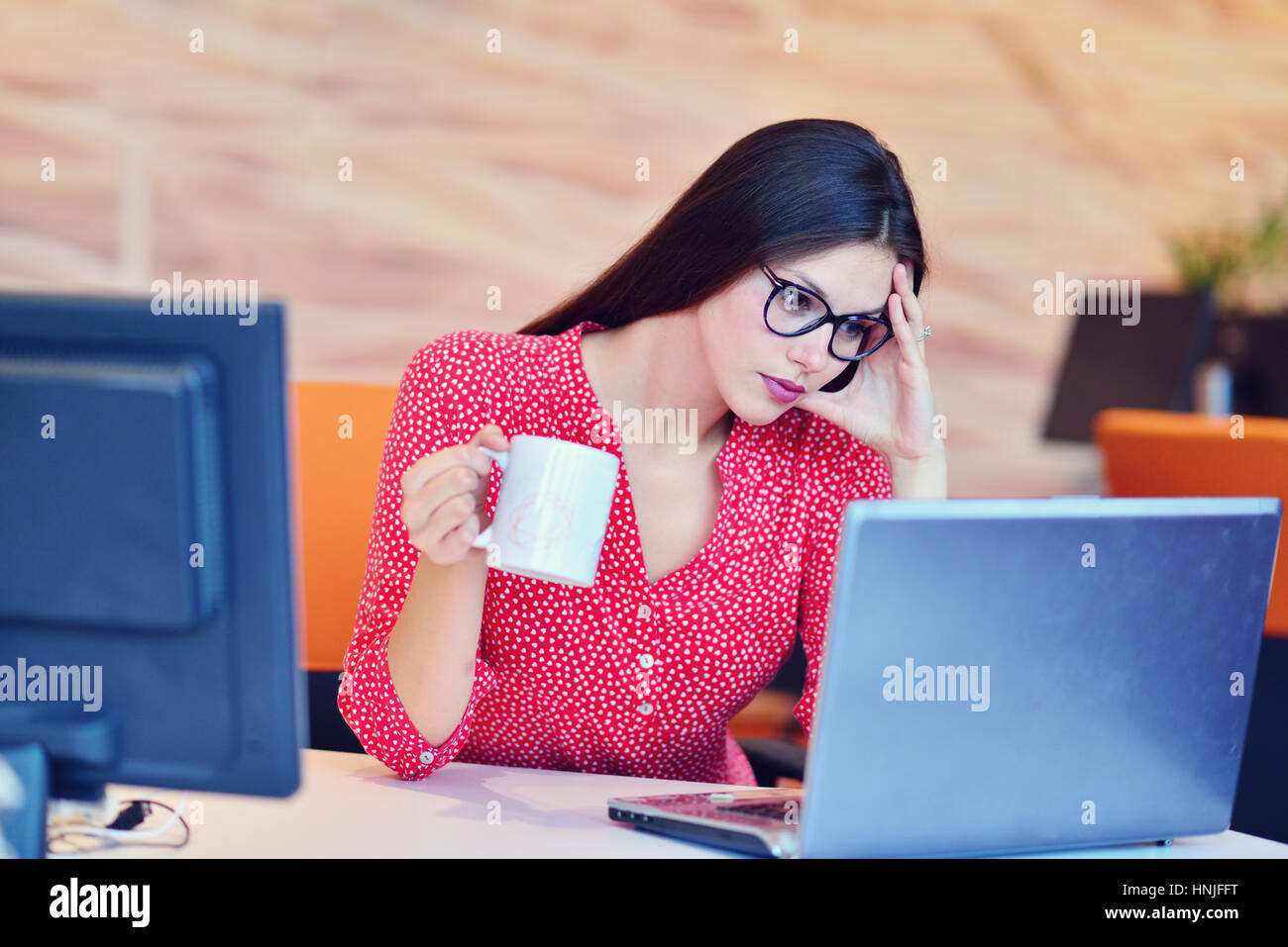 Tired overworked businesswoman at office covering her face with hands - Stock Image