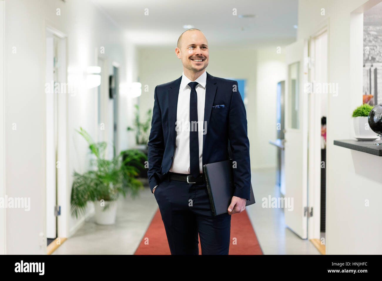 Swedish caucasian man in suit and tie. Scandinavian European ethnicity. Indoor offices. Smiling and carry laptop. - Stock Image