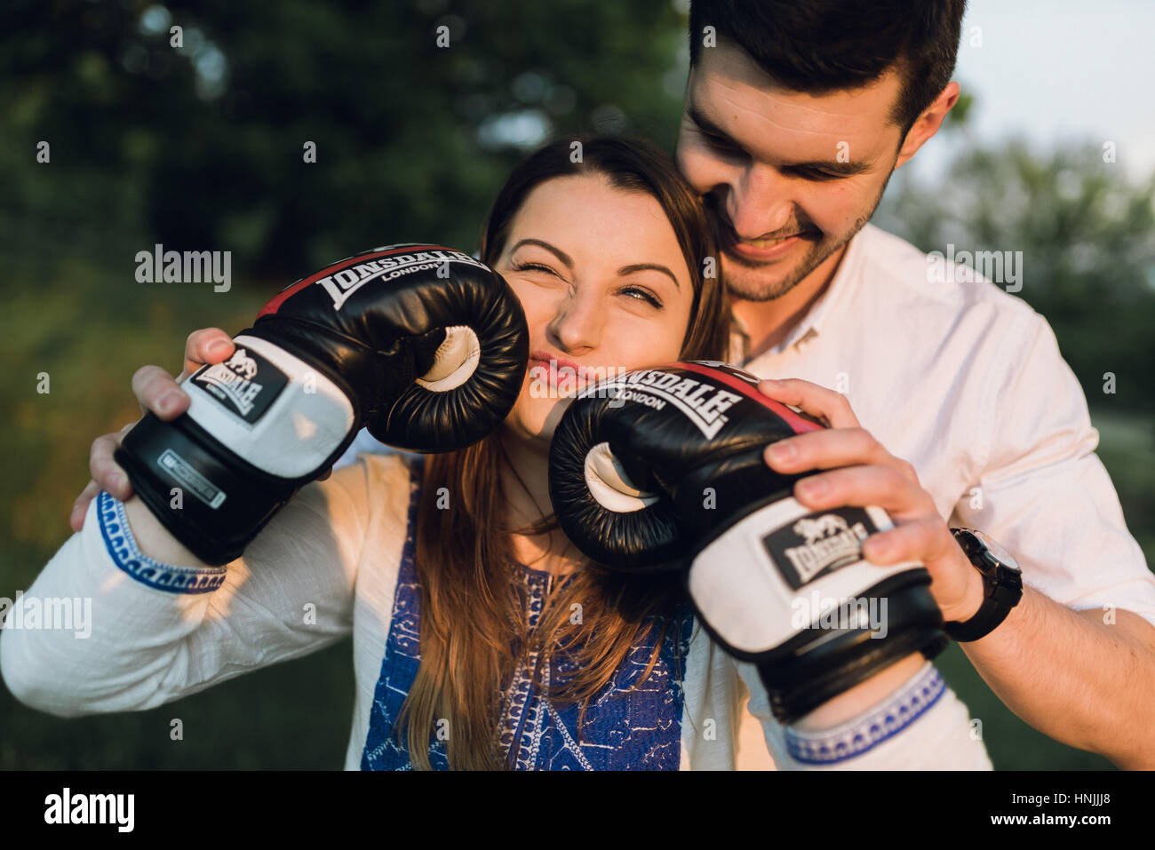 Young couple having fun with black boxing gloves, making funny faces - Stock Image