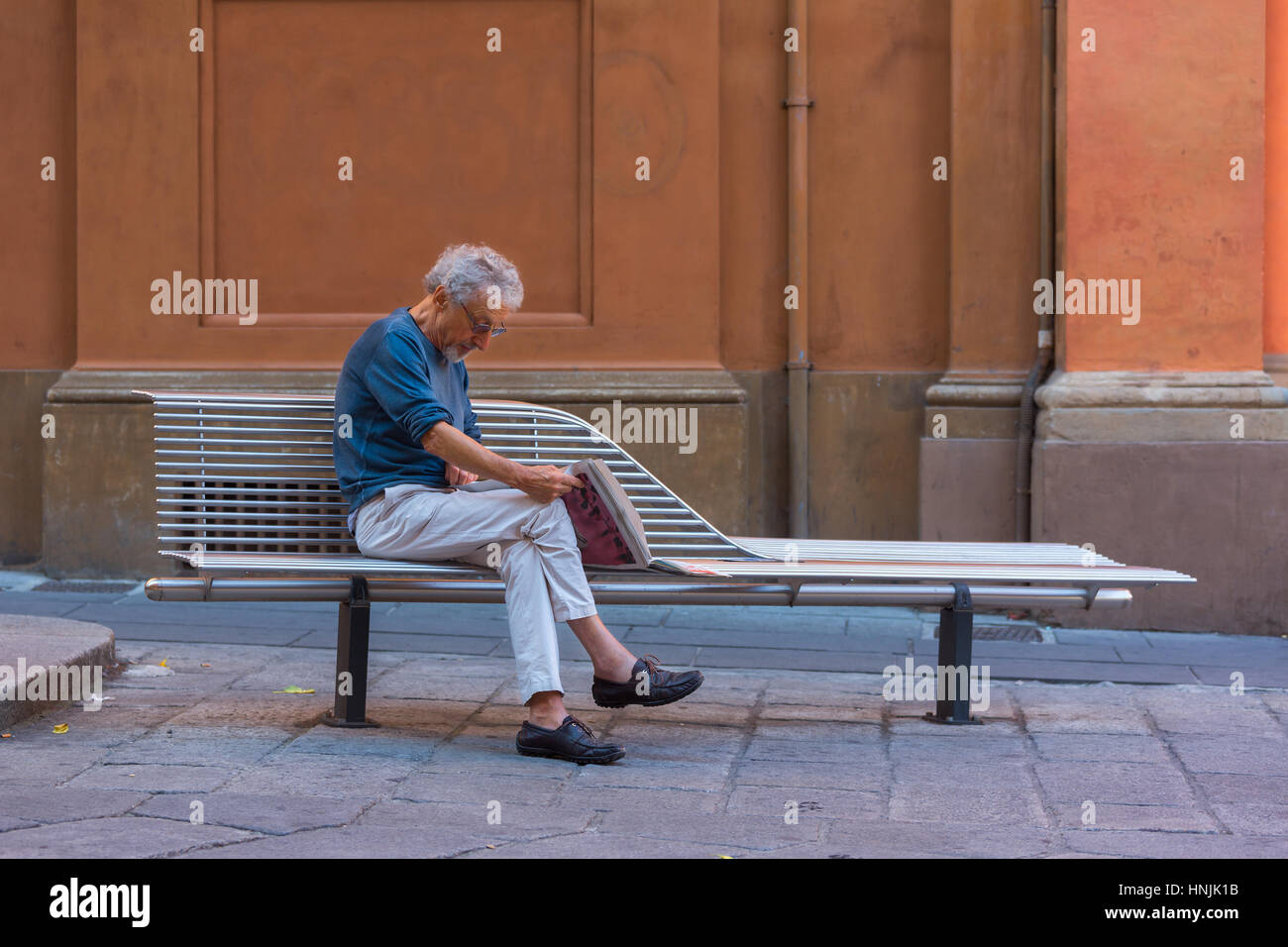 Man sits on a bench and reads newspaper in a tranquil environment of Bologna city. - Stock Image