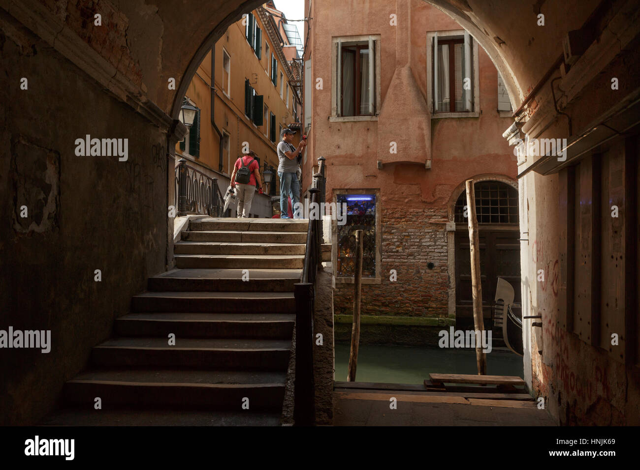 Tourist and groups roams the narrow streets of Venice.Many tourists take gondola tours to wander around the canals - Stock Image
