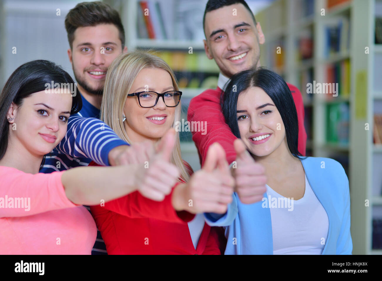 Cheerful group of students smiling at camera with thumbs up, success and learning concept - Stock Image