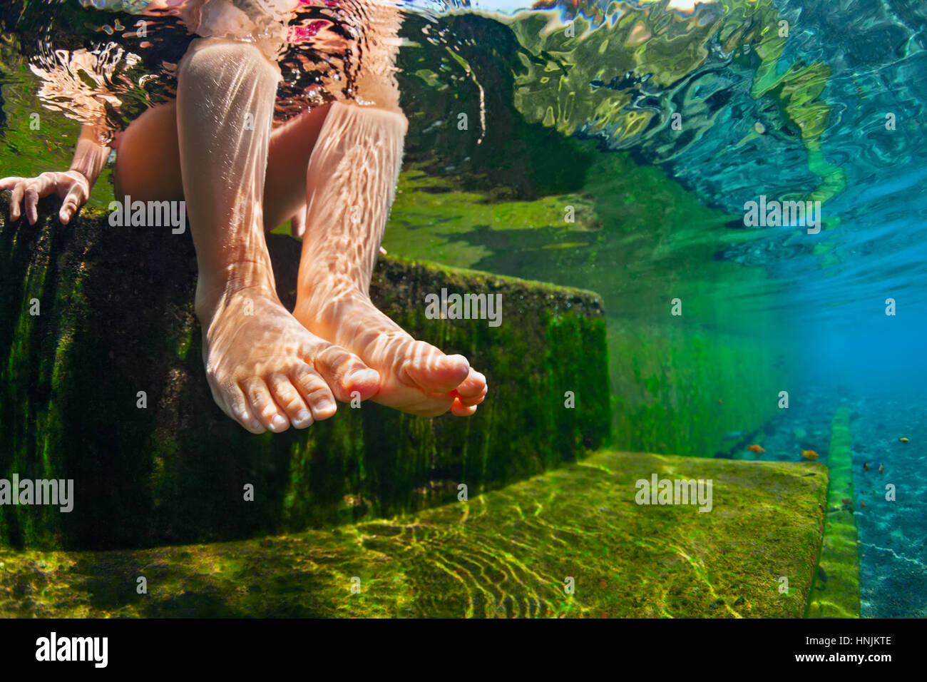 Happy person have fun at poolside edge. Funny under water photo of baby bare feet in natural pool. Family lifestyle. - Stock Image