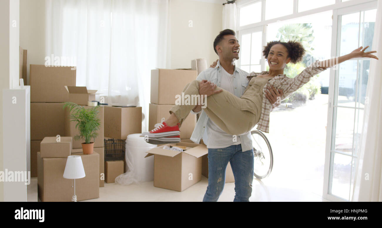Ecstatic young couple celebrating their new home with the young man holding his wife in his arms as she grins and - Stock Image