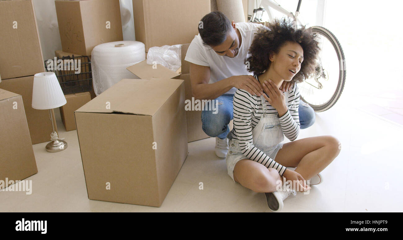 Husband massaging the neck of his wife as she sits cross legged on the floor grimacing in pain after straining her - Stock Image