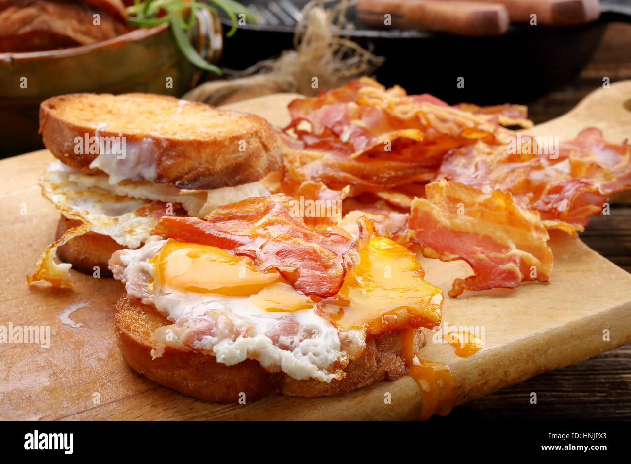 Sandwich with fried egg and hot bacon pieces on wooden background - Stock Image