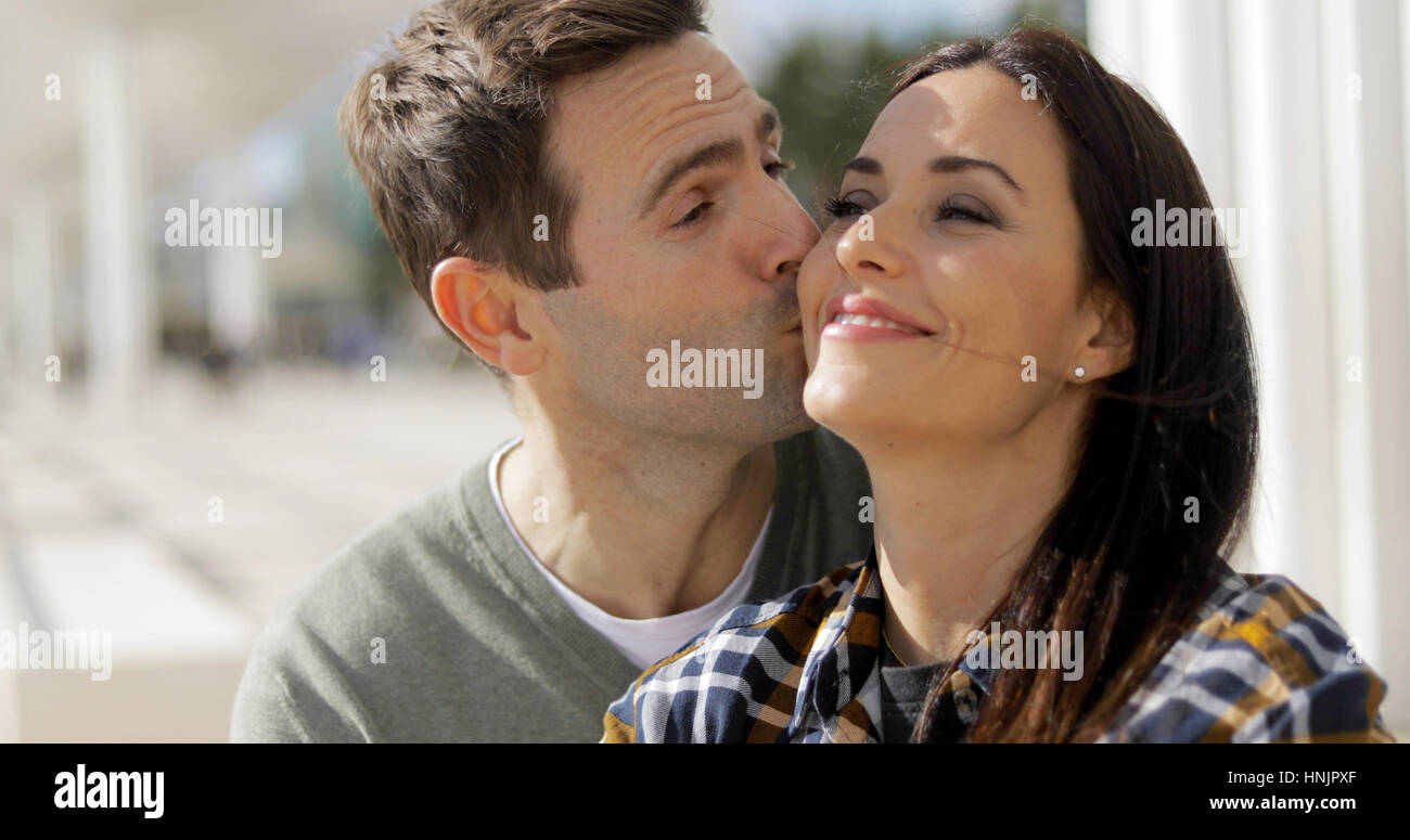 Amorous young man kissing his girlfriend on the cheek as she grins happily while they relax outdoors together - Stock Image