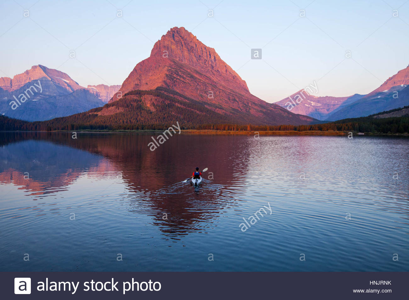 A kayaker on Swiftcurrent Lake watches the sunrise over Mount Grinnell. - Stock Image