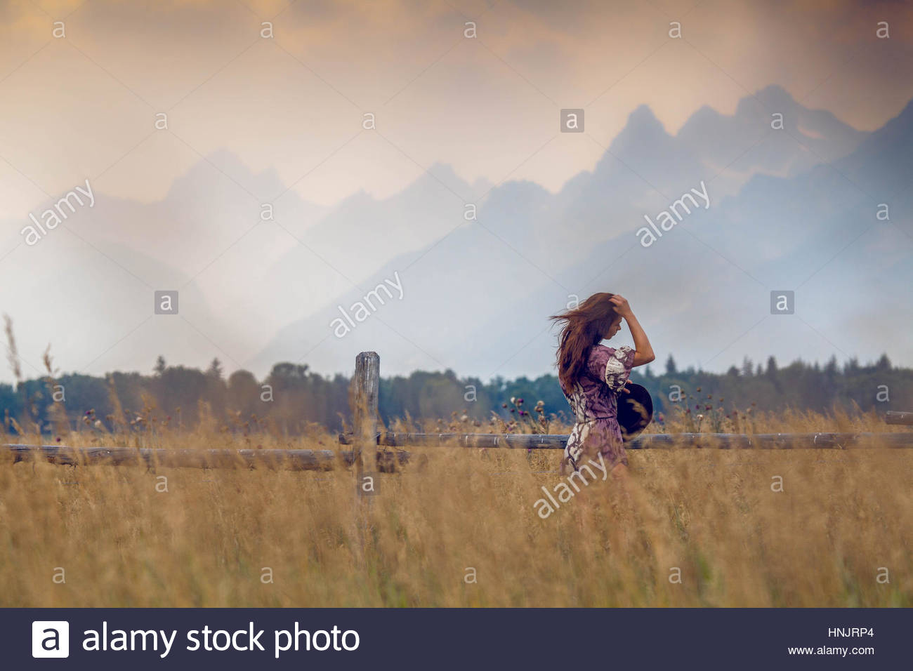 A woman watches a storm brew over the Tetons. - Stock Image