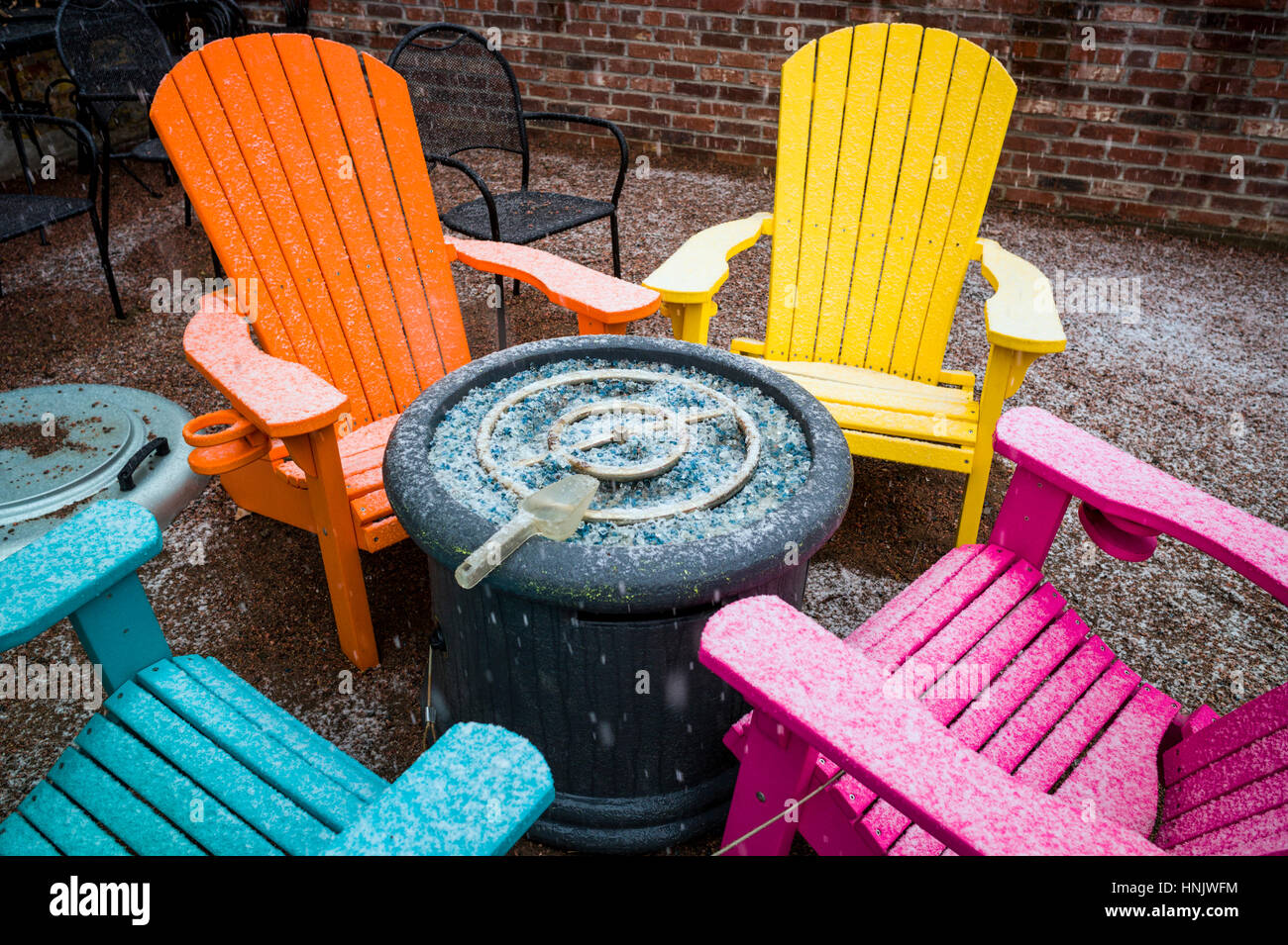 Colorful outdoor chairs in snow on patio of Boathouse Cantina restaurant; Salida; Colorado: USA - Stock Image