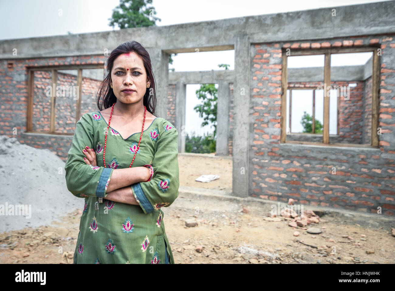 A woman poses for camera in front of an unfinished house for the 2015 earthquake victims in Chandani Mandan village, - Stock Image