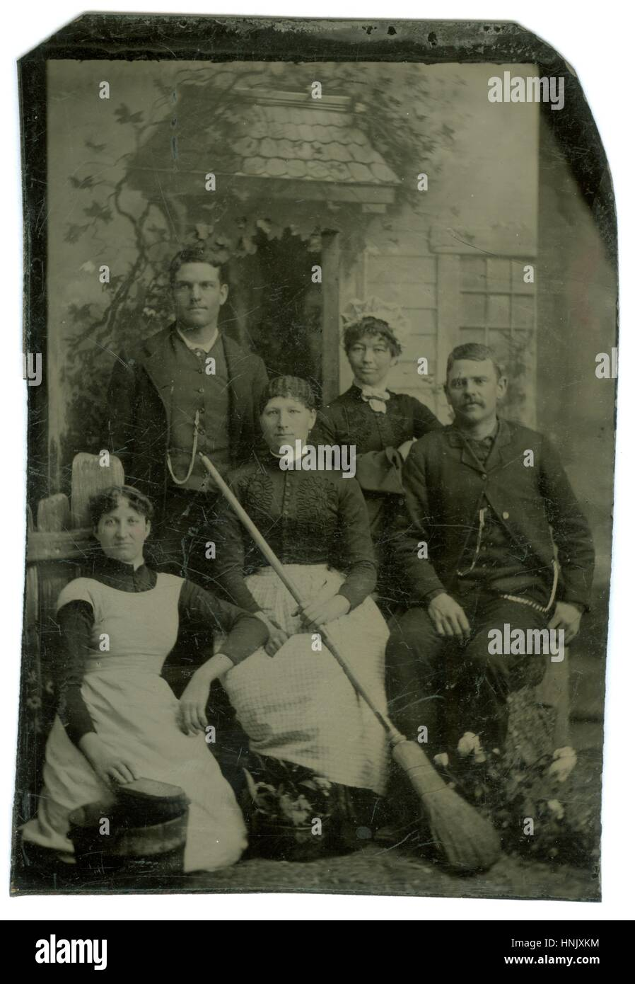 Housekeeping staff having their photo taken,1860s. Note the scrub bucket and brush lower left, posed flowers next - Stock Image