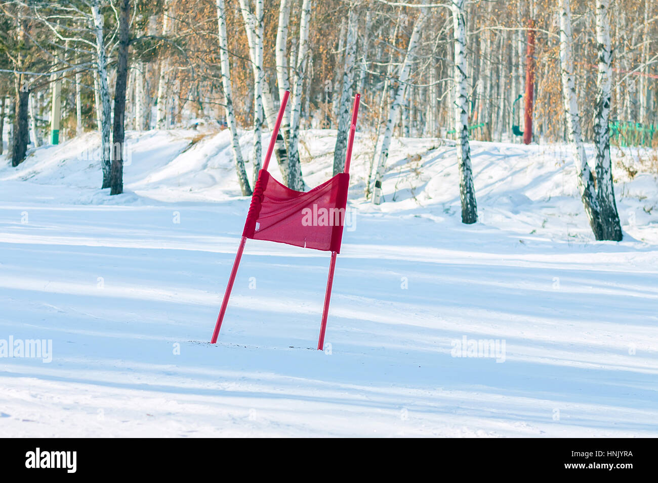 Slalom flag standing in the snow on the ski slopes. - Stock Image