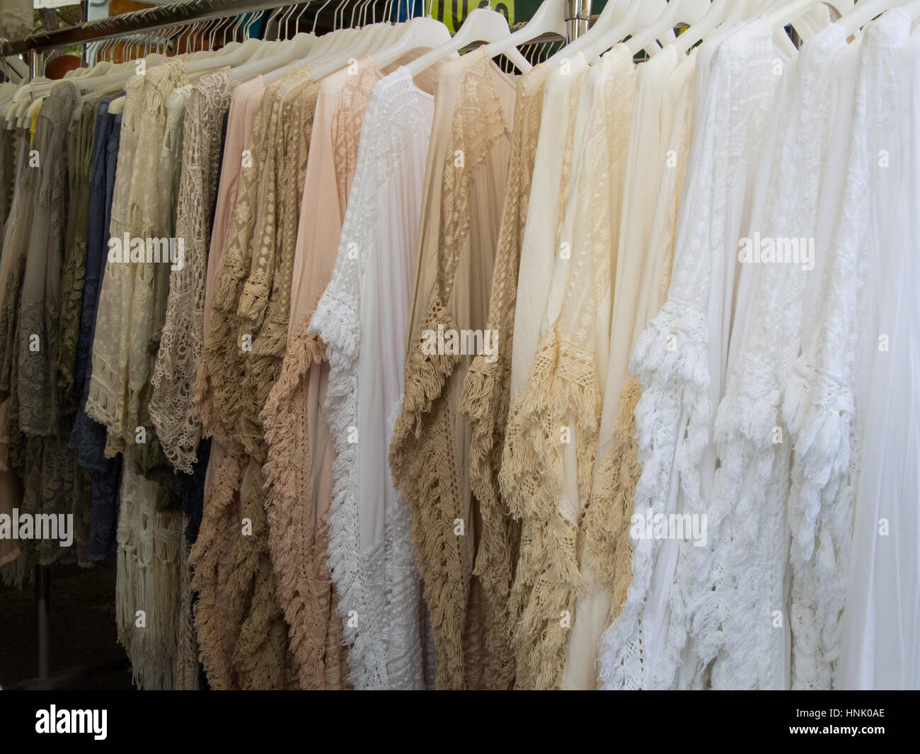 group of fringed clothes for woman in soft colors for sale in a market on a rack - Stock Image